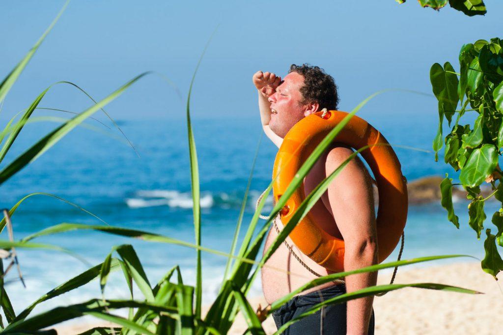 orange safety ring on man shoulder near body of water