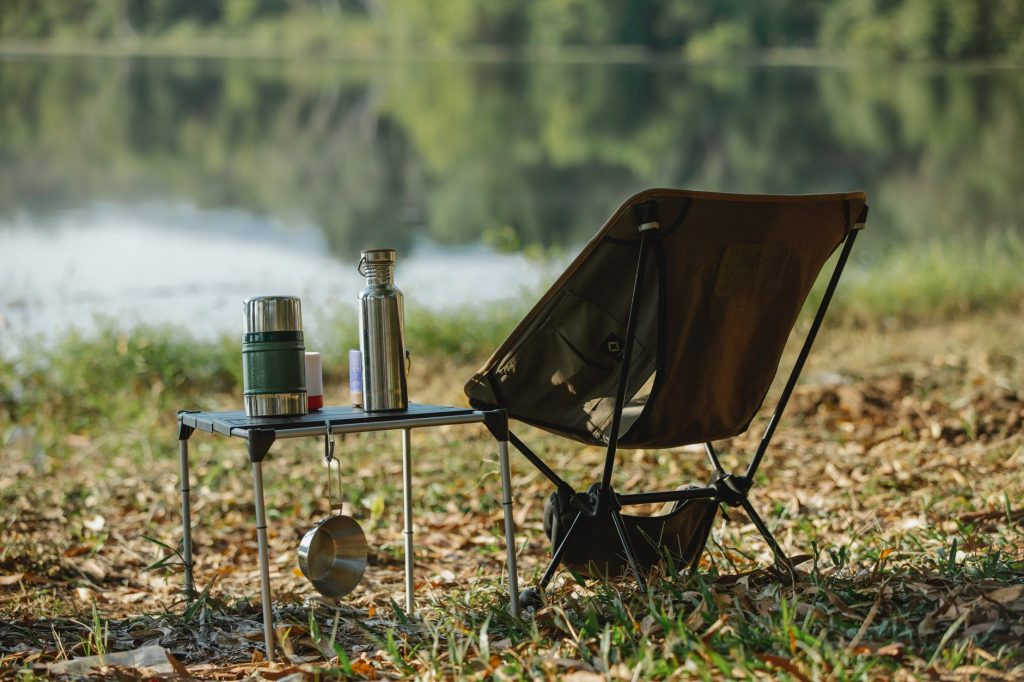 camping chair near table on river shore
